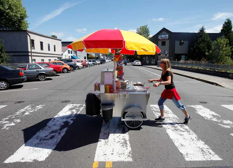 TIMES PHOTO: JONATHAN HOUSE - Susan Saunter crosses the street with her hot dog cart Quite Frank-ly on Main Street in downtown Tigard. Saunter is the newest food cart in Tigard, moving her hot dog stand up and down Main Street. More and more food carts are slowly making their way to Washington County where they see room for expansion.