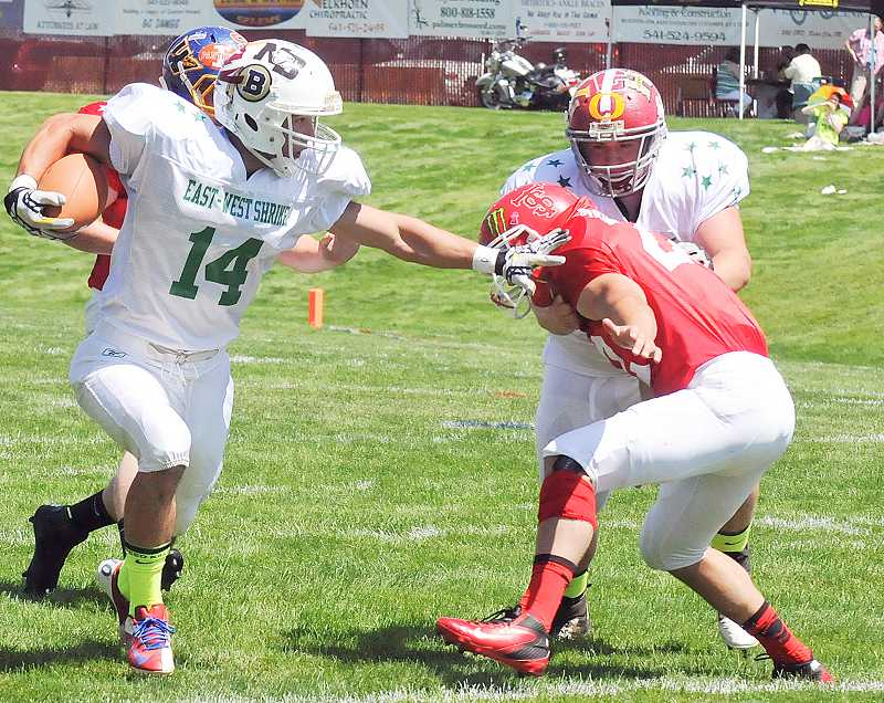 by: PHOTO BY KATHY ORR/BAKER CITY HERALD - Madras graduate Devin Ceciliani, in white for the West All-Stars, stiff-arms the East All-Stars' Cye Yates, of Coquille, during the 61st Oregon East-West Shrine football game Saturday in Baker City. Ceciliani caught six passes for 180 yards and two touchdowns to lead the West to a 33-23 win.