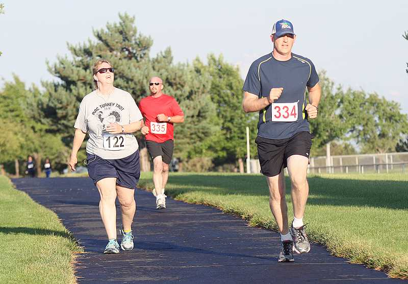 by: PHOTO BY JOE MCHANEY FOR THE PIONEER - Rich Affeldt, Bib No. 334, and Tammie Schongalla, 122, compete in the Madras Pioneer 'Beat the Heat' 5/10K run/walk on Saturday at Juniper Hills Park in Madras. Affeldt placed third in the 10K run, which is part of the Madras Aquatic Center Recreation District 10K race series. Schongalla was third in the 5K