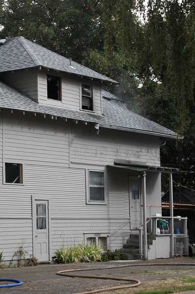 by: LINDSAY KEEFER - Firefighters attack the back of this house at 453 Montgomery St., where a fire started Thursday morning. The gutters are still in need of repair after another fire attacked the house from the front 21 months ago.