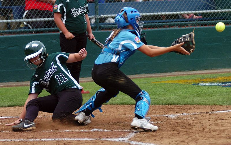 by: DAN BROOD - PLAY AT THE PLATE -- Tualatin City catcher Ella Hillier (right) looks to grab the ball as Central's Gabrielle Shackelford slides home in Thursday's Little League World Series contest.