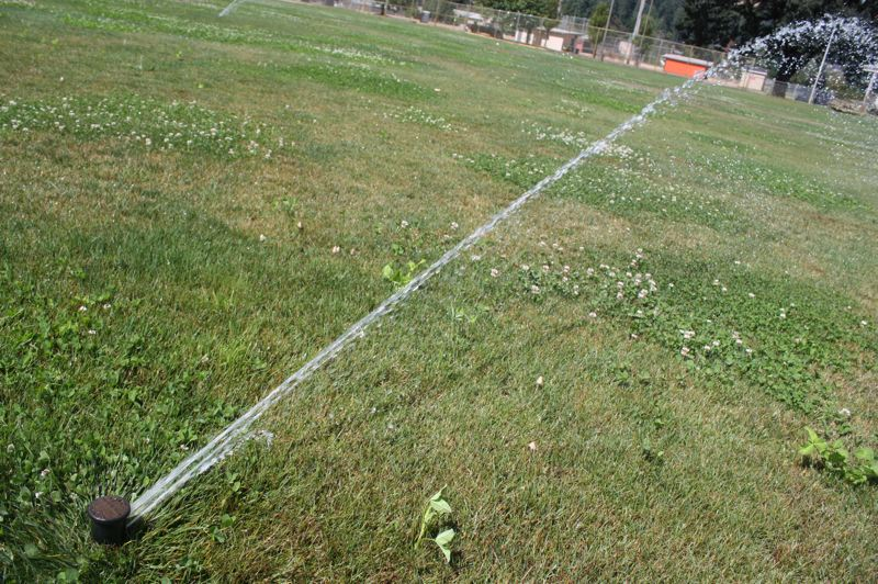 by: SPOTLIGHT PHOTO: ROBIN JOHNSON - One of many sprinklers at Scappoose Middle School casts water across the schools green field on Aug. 7 at noon. Under mild curtailment reduction measures, lawn watering would be restricted to evening hours.