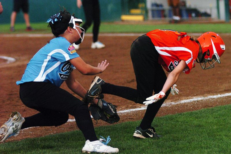 by: DAN BROOD - GOT HER -- Tualatin City third baseman Lily Marshall (left) tags out Southeast's Kate Haas in a rundown during the second inning of Friday's game at the Little League Softball World Series.