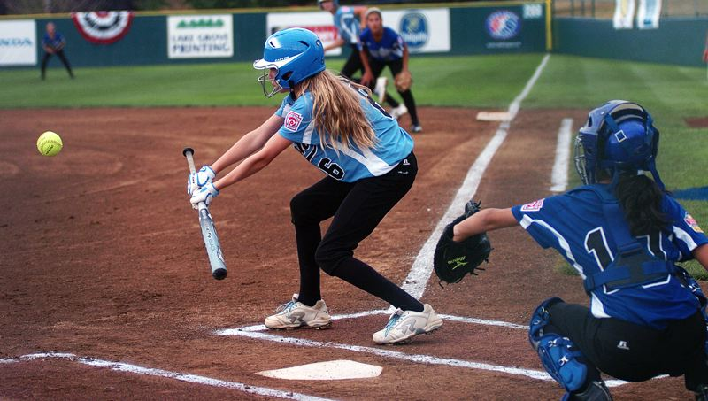 by: DAN BROOD - SMALL BALL -- Tualatin City's Camille Hall puts down the first of her two bunt singles during the team's 7-1 win over Italy Saturday at the Little League Softball World Series.