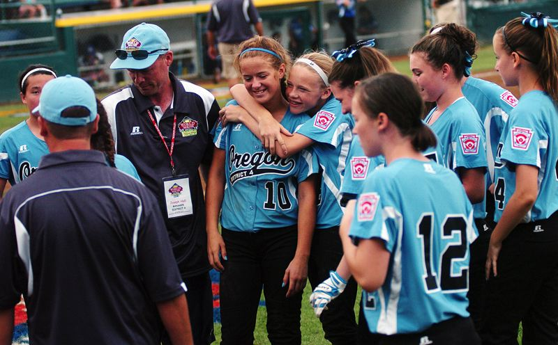 by: DAN BROOD - HAPPY TIMES -- Tualatin City's Lindsay Stadick (10) gets a hug from Camille Hall following the team's 7-1 win over Italy Saturday at the Little League Softball World Series. Stadick had two hits, including a triple, in the victory.