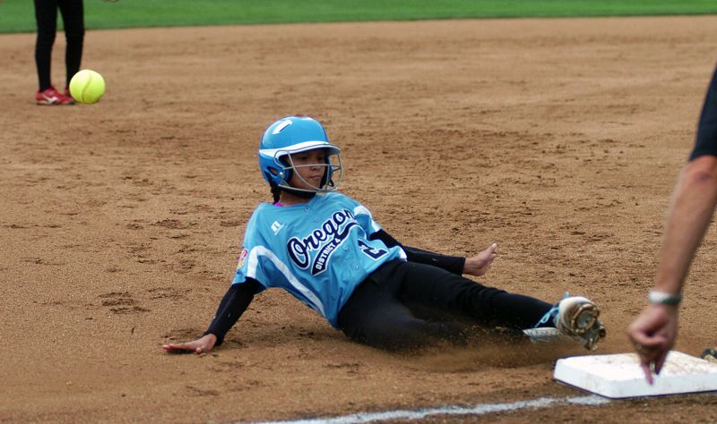 by: DAN BROOD - SLIDING SAVE -- Tualatin City's Kendra Zuckerman slides safely to third base as the ball zips past her during Sunday's game at the Little League Softball World Series.