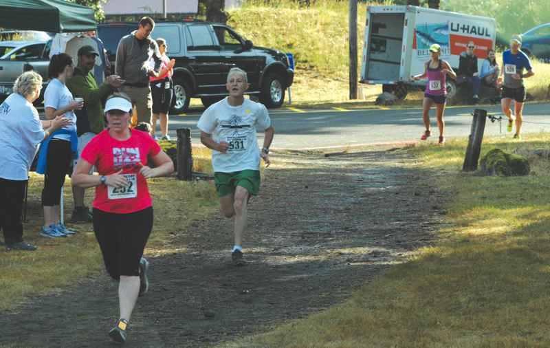 by: SANDY POST: PARKER LEE - A line of runners come up a wood-chip trail to the finishing chute.