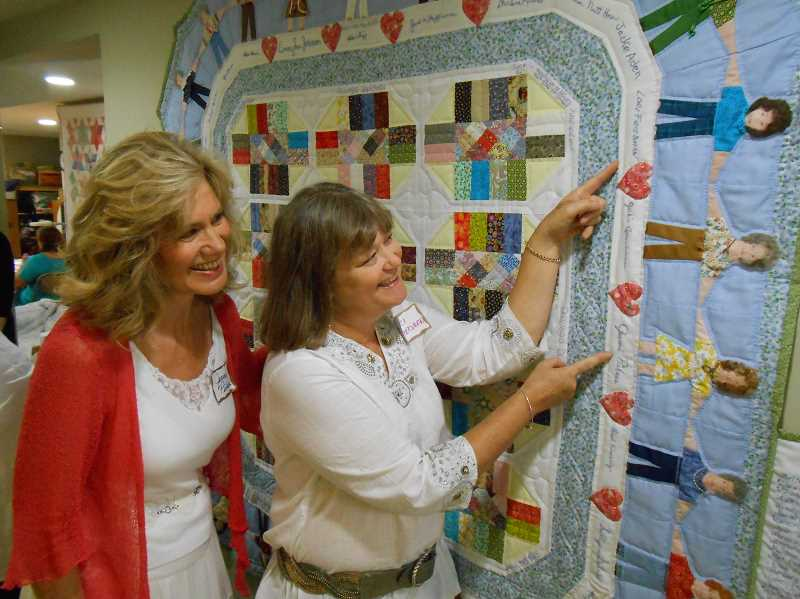 by: CLIFF NEWELL - Lori Friedman, right, points to the figures depicting herself and the quilt's maker, Jeannie Pickens, left. This beautiful work sums up what Oswego Quilters is all about.