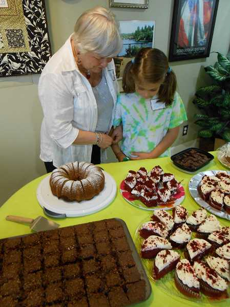by: CLIFF NEWELL - Carol Hull and her granddaughter, Libby Hull, are dazzled by the display of cakes at the reunion luncheon. Club members have long known that one cannot live by quilting alone.