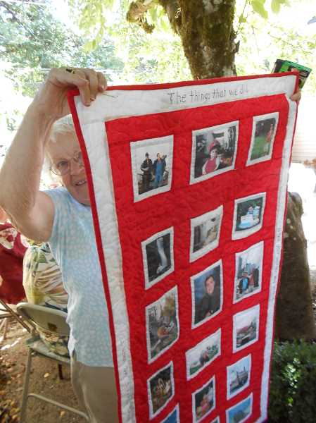 by: CLIFF NEWELL - Jane Johnson peeks out from behind the quilt she designed that shows the history of her family.