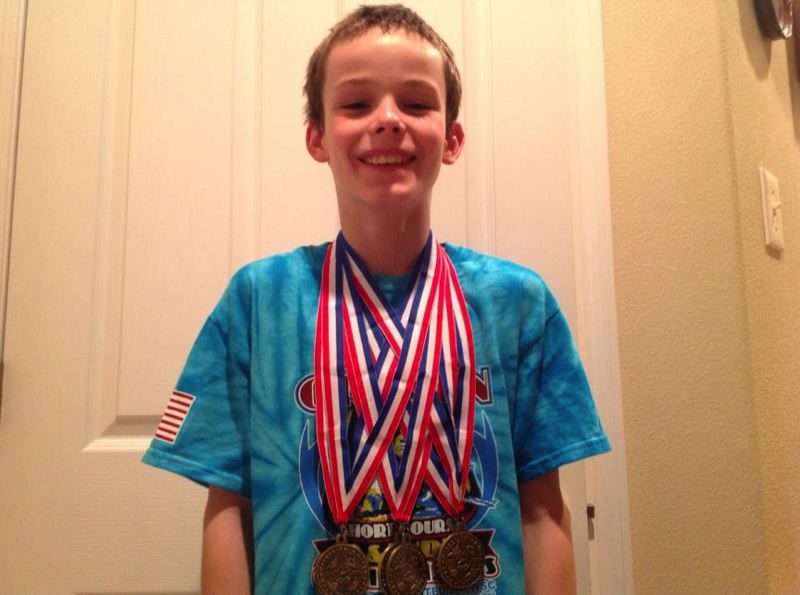by: SUBMITTED PHOTO - Ten-year-old Ian Watt from Oregon City shows off his hardware after the at the recent State Swim Championship meet.