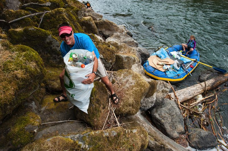 by: PHOTO BY MARK GAMBA - A volunteer climbs on rocks to pick up trash next to the Clackamas River.
