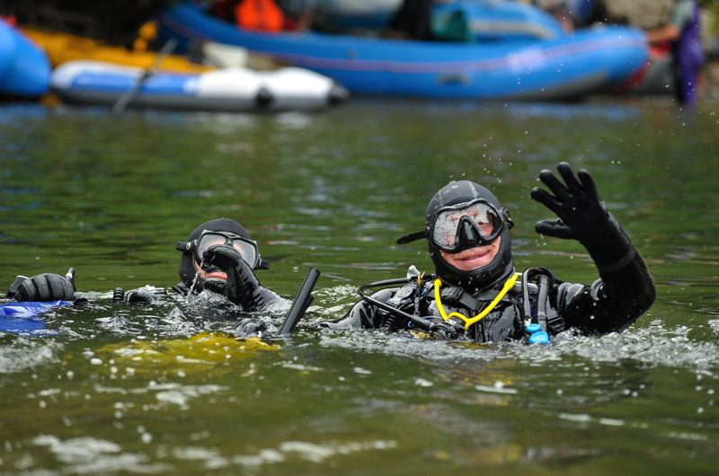 by: PHOTO BY MARK GAMBA - Two scuba divers rise from the waters of the Clackamas collecting trash from the bottom of the river, at last year's clean-up activity.