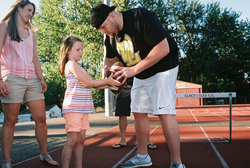 by: PHOTO BY: JOHN DENNY - FRIENDLY RIVALS: David Cote, team captain for West Linn High School's alumni football team, gives Oregon City 4-year-old Josephine Clark some instruction in how to hold a football as the two kindred spirits met for the first time recently in Oregon City. Josephine, who is the honorary captain for Oregon Citys alumni football team, and Cote both have cystic fibrosis.