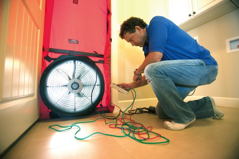 by: PAMPLIN MEDIA GROUP: JONATHAN HOUSE - Peter Brown, Earth Advantage Institute director of residential services, uses a blower door to  measure air leakage in a new Bull Mountain house. The nonprofit is so sure of its energy projections that its guaranteeing utility bills wont top estimates.