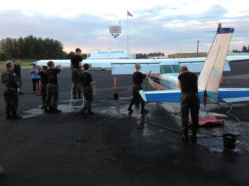 by: SUBMITTED PHOTO - CAP cadets receive hands-on aeronautics education, learning to fly and maintain aircraft, including washing an airplane on July 16.