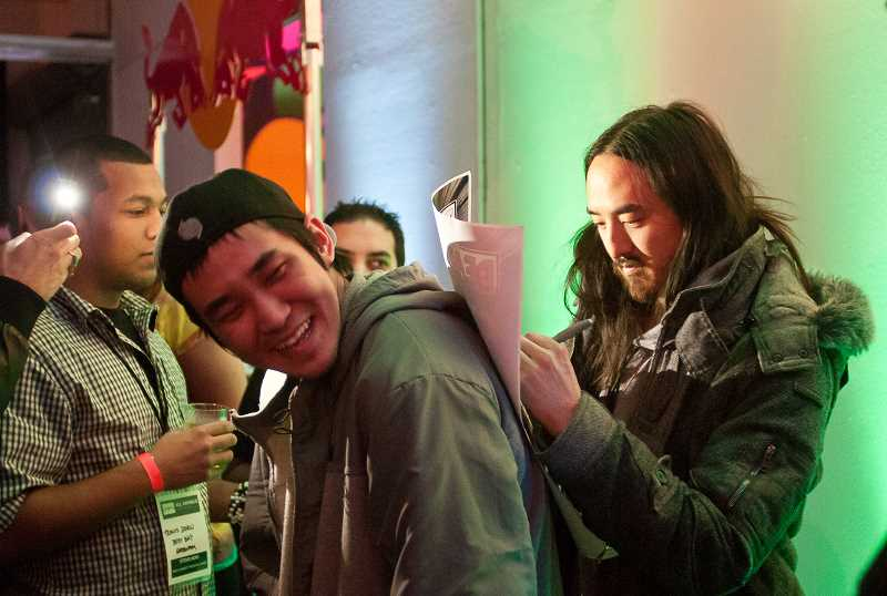 by: JOSH KULLA - DJ Steve Aoki, right, signs an autograph at Sol Republic headquarters during a party celebrating the release of the companys Tracks headphones in 2012.
