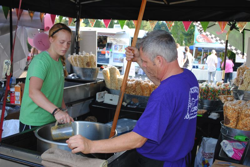by: NEWS-TIMES PHOTO: STEPHANIE HAUGEN - Jordyn Brenheman and Mike Jodoin of Miss Hannahs Gourmet Popcorn Co. roasted up garlic kettle corn during their first year vending at the festival.