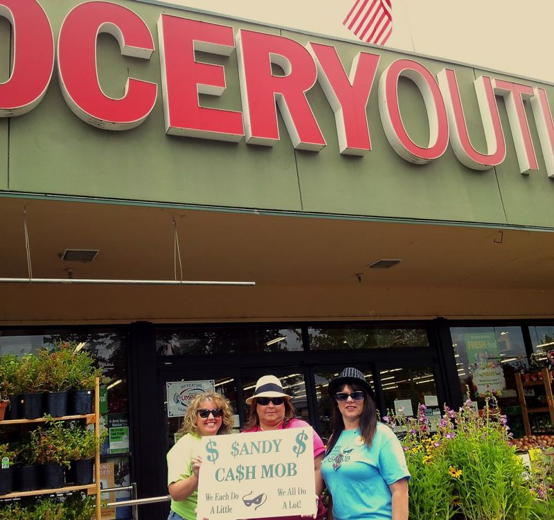 by: CONTRIBUTED PHOTO - A trio of cash mobbers gather early to remind shoppers that a one-hour cash mob is needed at 11 a.m. Saturday, Aug. 17, at the Sandy Grocery Outlet store, 36701 Highway 26. Pictured, from left, are Lacy Renard, Lisa Foster and Debbie Grimes from the Sandy Area Chamber of Commerce.