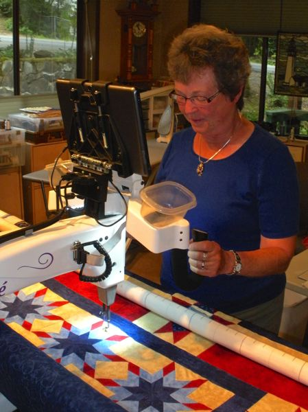 by: POST PHOTO: JIM HART - Jean Ludeman of Welches guides the stitching on her computerized quilting machine as she creates a twin-size quilt of valor.