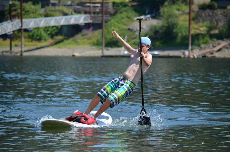 by: KEVIN KING - Kyle Del Fatti, a student at Lakeridge High School, makes a thrilling turn at the midway point of the Stand Up to NF paddleboard race fundraiser on Aug. 4.