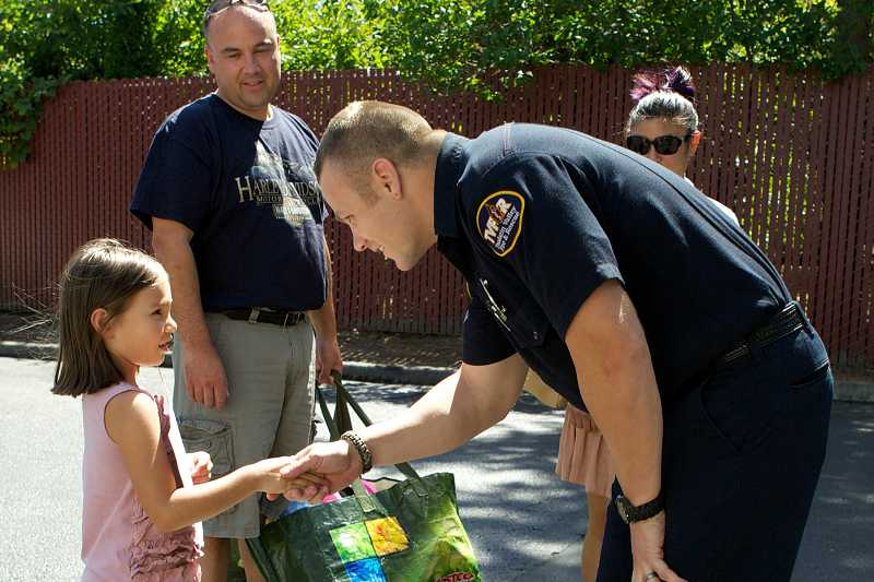 by: TIMES PHOTO: JAIME VALDEZ - Rod and Valerie Ditchfield of Beaverton watch their daughter, Giselle, 6, shake TVF&R firefighter Levi McCubbins' hand at Station 68. Giselle donated new stuffed animals she got for her birthday to the fire station for firefighters to give to traumatized children.