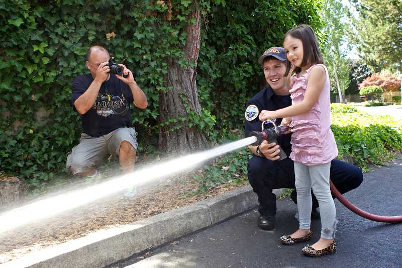 by: TIMES PHOTO: JAIME VALDEZ - Rod Ditchfield of Beaverton takes pictures of his daughter Giselle as she sprays a fire hose with the assistance of TVF&R firefigher Joe Muravez.