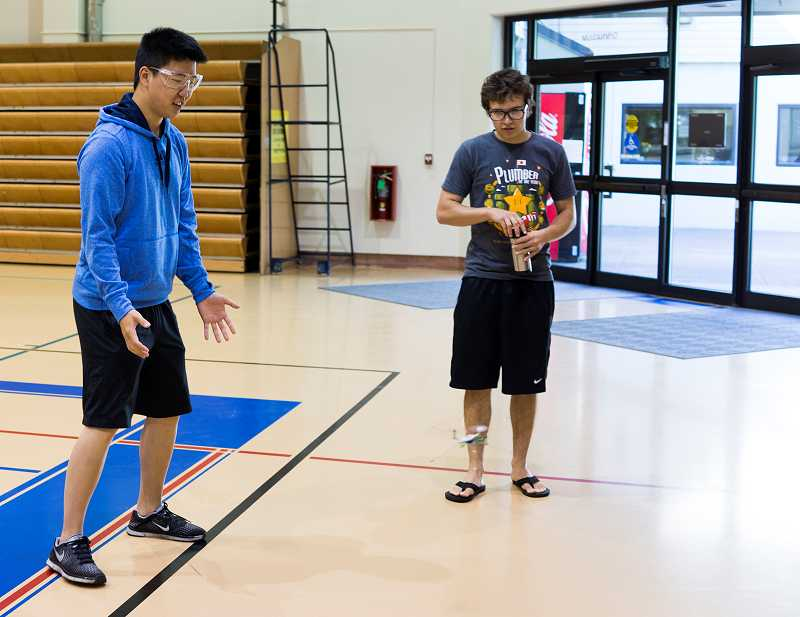 by: TIMES PHOTO: CHASE ALLGOOD - Daniel Kim, left, a sophomore at the Portland Community College Sylvania campus, reacts to the in-flight quad copter his team programmed during the Ultimate Engineering Experience camp on Tuesday morning at PCC's Rock Creek campus.