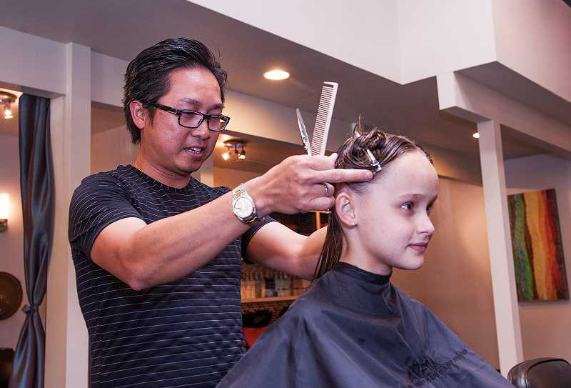 by: PAMPLIN MEDIA GROUP: JOSH KULLA - Brooklynn Oldroyd, 8, receives a haircut and style from GiGi owner Johnny Hoang on Aug. 4.