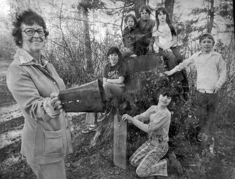 Mary E. (Betty) Cody shows one of her classes a school bell from Estacadas early history. A hand-written note on the back of th photograph explains that at the time (in 1974) the bell was more than 80 years old and was used to call students in from recess. This photograph is in Philip Foster Farm archives.