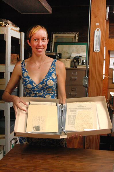 by: ISABEL GAUTSCHI - Philip Foster Farm intern Susie Trexler has spent the summer cataloging and archiving items donated to the farm by Mary E. (Betty) Cody. She displays an album of paper work from Estacada's early schools.