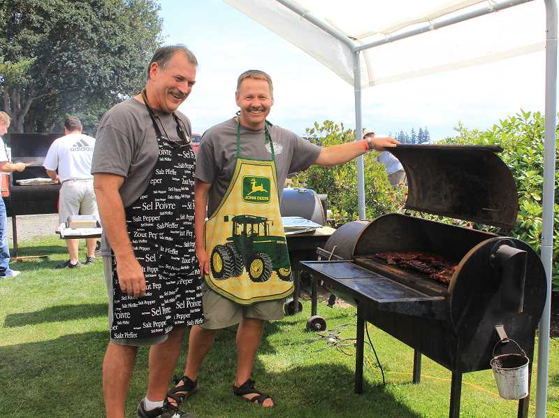 by: NIKKI DEBUSE - The sixth annual Firehouse Cook-Off at Wooden Shoe Tulip Farm hosted 12 teams Saturday. (Above left) Paul Iverson, Woodburn Fire Chief (at the grill) and former Woodburn Police Officer Jason Tlusty cook up some meats.