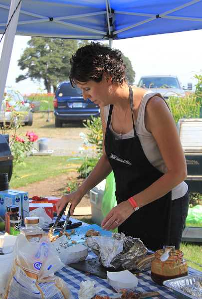 by: NIKKI DEBUSE - Gina Audritsh serves some barbecue chicken at the Firehouse Cook-Off. Audritsh's team, Something's Burning, won Grand Champion and also consists of James Audritsh, Andrea Audritsh, Mark VanLieu and Uli Reich.