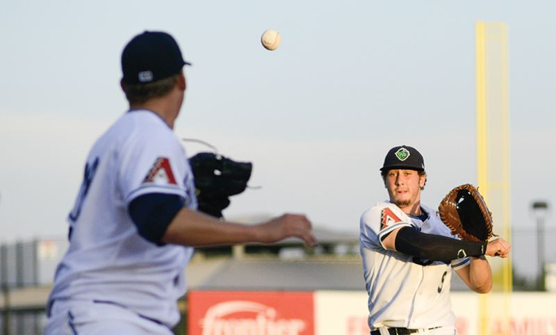 by: HILLSBORO TRIBUNE PHOTO: CHASE ALLGOOD - Hillsboro Hops first baseman George Roberts makes a throw to pitcher Ross Gerdeman, who is covering first base, during Monday's 2-0 victory over the Tri-City Dust Devils.