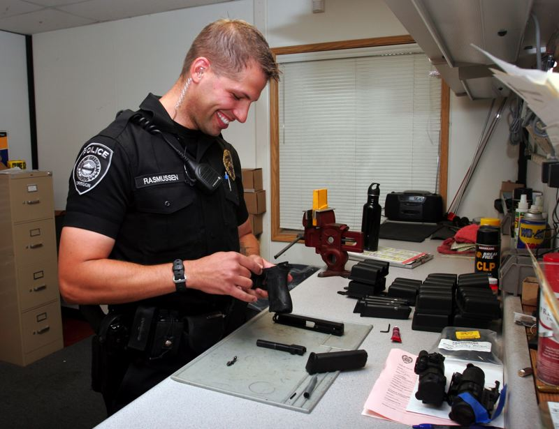 by: OUTLOOK PHOTO: JIM CLARK - Officer Ryan Rasmussen inspects a weapon in the police armory. Rasmussen is Gresham Police Officer of the Year.