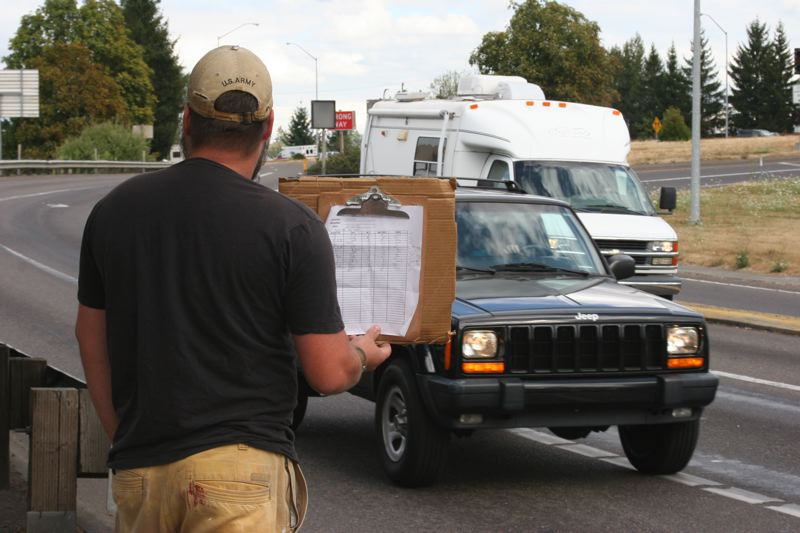 by: SUBMITTED PHOTO - David Spears goes undercover, hiding his notes behind a handmade sign, to study panhandling at the Interstate 205 off-ramp into downtown Oregon City for his book 'Exit Ramp.'