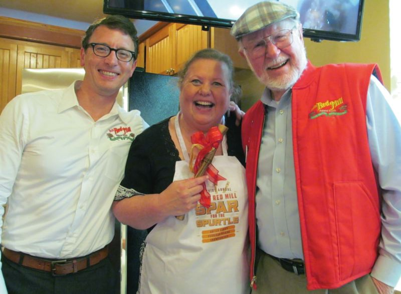 by: PHOTO BY ELLEN SPITALERI - Matt Cox, left, marketing director for Bob's Red Mill, and Bob Moore, founder of the company, congratulate winner Paula Todora.