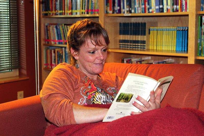 by: OUTLOOK PHOTO: CARI HACHMANN - Kim Schoenes new favorite hobby is reading in the library of the womens shelter.