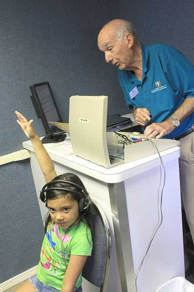 by: JEFF MCDONALD  - Heaven Karúo, 6, of Mount Angel, gets her hearing tested as part of the Oregon Lions Sight & Hearing Mobile Screening program Saturday in Mount Angel. Karúo is one of dozens who had their vision, hearing and glucose levels screened free-of-charge for possible health risks.
