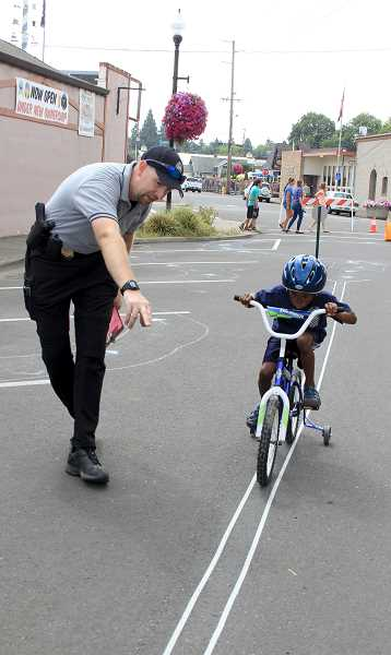 by: JEFF MCDONALD - Sgt. Jeff Charpilloz of Mount Angel Police Department gives Gabriel James, 6, instructions during the Bike Rodeo event last weekend in Mount Angel. The department gave out about 70 free bike helmets as part of the event.