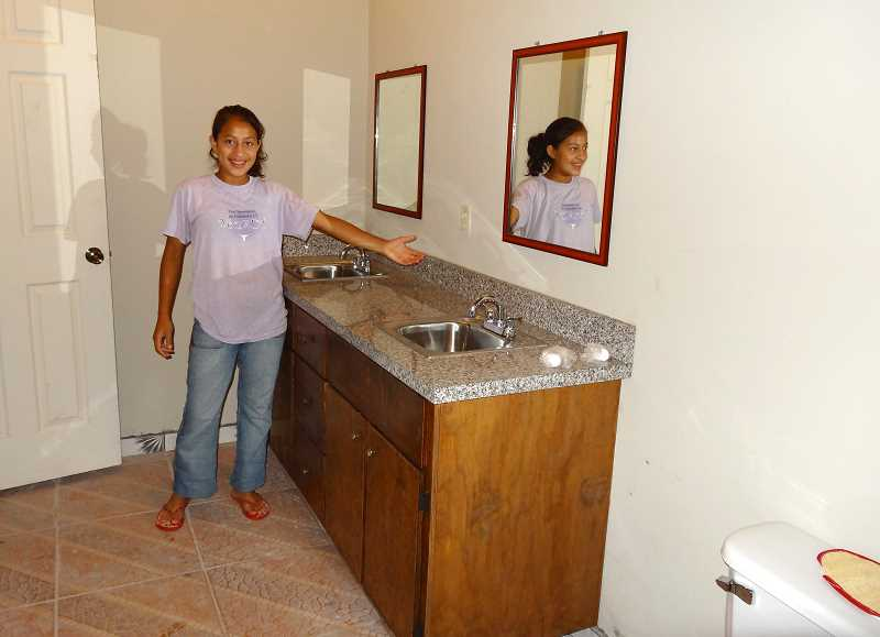 by: COURTESY OF WOODBURN FOURSQUARE CHURCH - The church volunteers helped build and install bathroom cabinets in the girls dormitory while in Honduras, as presented by orphan Esther.