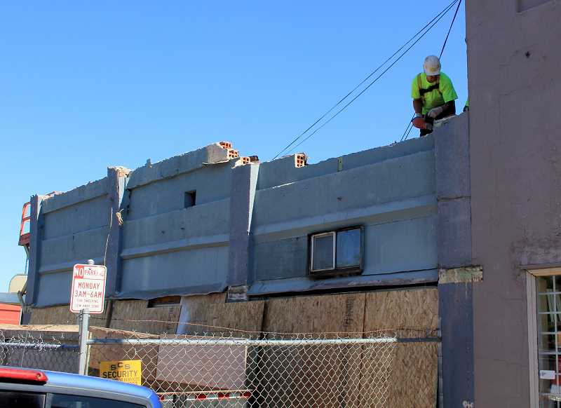 by: JEFF MCDONALD  - A worker from Woodburn-based Triplett Wellman Contractors dismantles an unstable portion of Mayor Kathy Figleys building on Grant Street Monday.