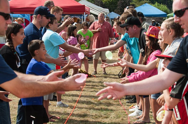 by: CONTRIBUTED PHOTO: BRIAN PASKO PHOTOGRAPHY - In this water balloon toss game, participants risk taking a shower in public, but that risk is half of the fun at this Boring Celebration activity — one of many designed to bring smiles to all who celebrate the arrival of fall.