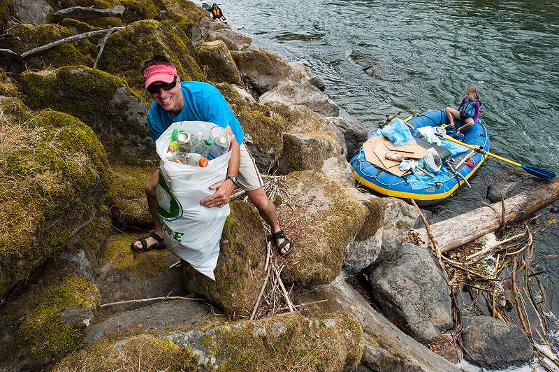 by:  MARK GAMBA - A volunteer climbs on rocks to pick up trash next to the Clackamas River.