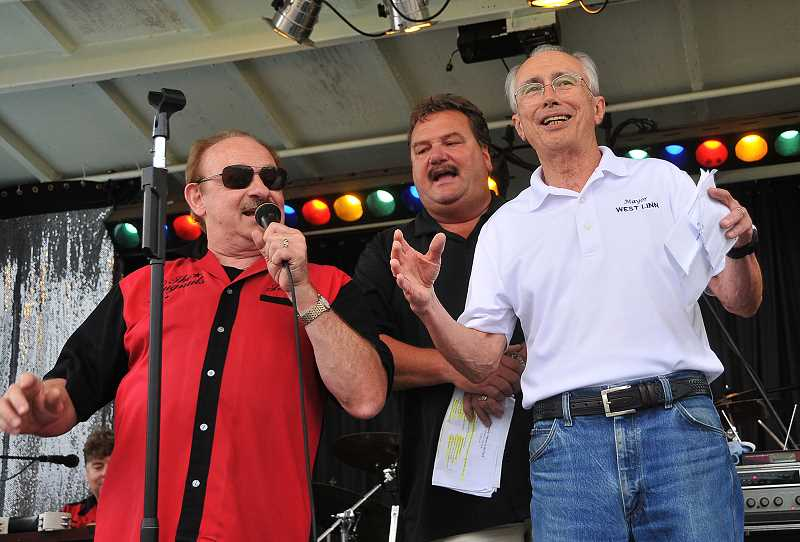 by: STAFF PHOTOS: VERN UYETAKE - West Linn Mayor John Kovash, right, joins DJ Scott Tom, center, and Jerry Hoffman of Johnny Limbo and the Lugnuts in singing 'Happy Birthday' to West Linn to kick off the centennial celebration Thursday evening at Tanner Creek Park.