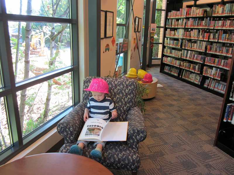 by: WEST LINN PUBLIC LIBRARY - Will Schoepper, 2 1/2, checks out a book about construction equipment while sitting in the library's new construction viewing station. Kids of all ages can look out the windows and watch the new parking lot being built adjacent to the library. There are even yellow and pink hard hats for kids to sport.