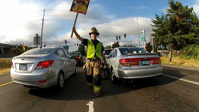 by: TUALATIN VALLEY FIRE & RESCUE - Tualatin Valley Fire & Rescue firefighters asked West Linn commuters for donations for the Muscular Dystrophy Association.