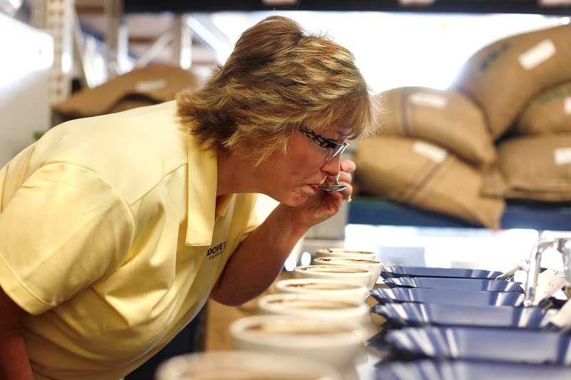 by: TIMES PHOTO: JONATHAN HOUSE - Dovetail Coffee's Cathy Zellmer tests different brews during a cupping at her roasting facility on Southwest Nimbus Avenue in Beaverton.