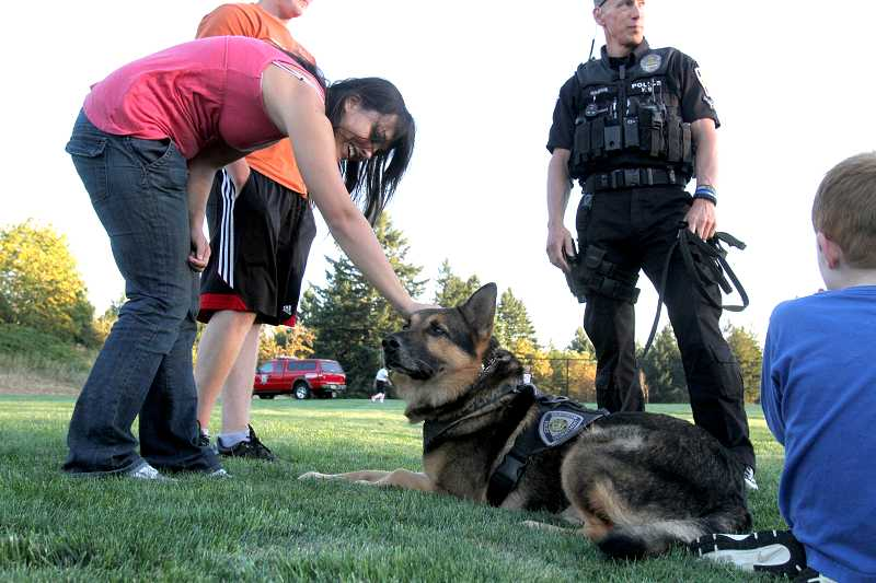 by: TIMES PHOTO: JONATHAN HOUSE - Jessica Mull gives a friendly pat to Beaverton Police K9 Jago during the grand opening party for Paul and Verna Winkelman Park near Cooper Mountain in Aloha.