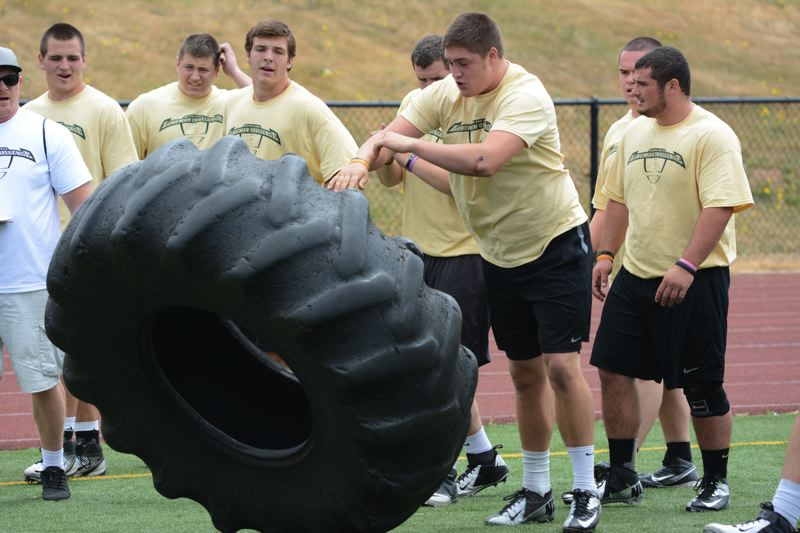 by: TIMES PHOTO: MATT SINGLEDECKER - Jesuit tight end Henry Mondeaux won the tire flip at the Metro Linemen Challenge with 13 attempts.